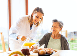 caregiver preparing food for senior woman