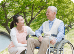 caregiver and senior man in a wheelchair smiling